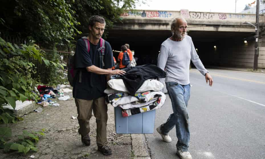 Jason Carmine, left, and his father Kevin Carmine, who say they both are addicted to heroin, carry their belongings from an encampment on Wednesday.