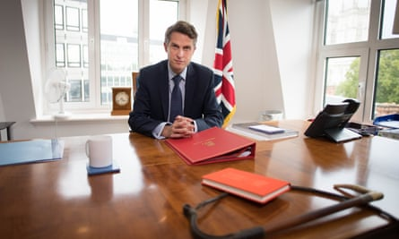 Gavin Williamson at desk with flag in background and whip in foreground
