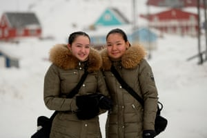 Two girls in warm coats pose for a photo