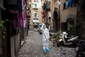 Naples, ItalyA healthcare worker wearing a protective suit walks through the Spanish Quarters of the city to screen people for coronavirus