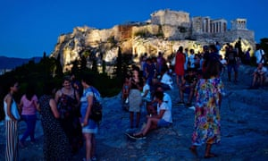 GREECE-TOURISM-FEATUREPeople visit the Aeropagus hill as the Acropolis is seen in the backround in Athens on August 6, 2018. / AFP PHOTO / LOUISA GOULIAMAKILOUISA GOULIAMAKI/AFP/Getty Images