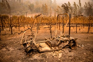 The remains of a golf cart burned by the Glass fire sits next to a vineyard at Calistoga Ranch.