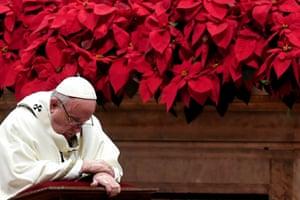 Pope Francis prays as he celebrates the Christmas mass