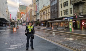 An officer guards deserted street in Melbourne after attack, which is being treated as a terrorist incident.