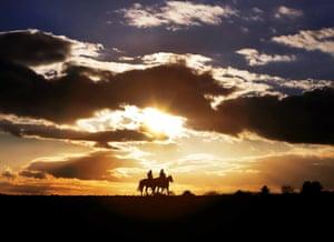 Oberursel, Germany Two women ride horses as the sun sets in Oberursel