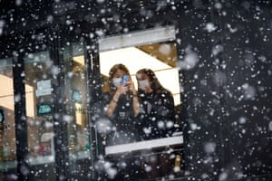 Seoul, South Korea A woman takes photographs of falling snow from a window