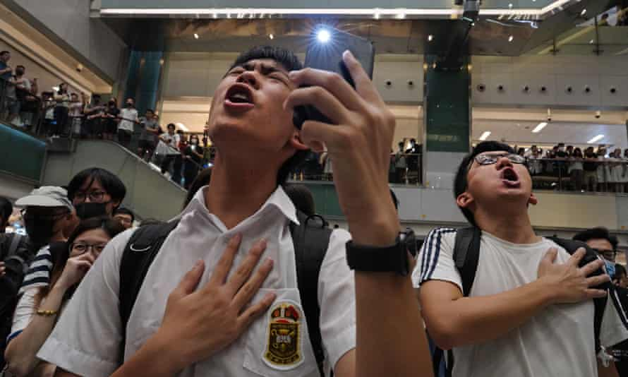 Hongkongers sing Glory to Hong Kong at a protest last year. It has now been banned from schools.