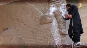 An IS militant destroys a 7th-century statue of a lamassu, an Assyrian diety, with a jackhammer in Mosul Museum, Iraq.