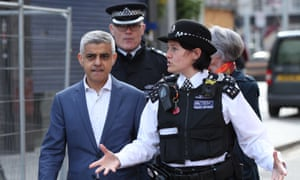 The London mayor, Sadiq Khan, talks to Met police officers. He has blamed austerity for decimating police services.