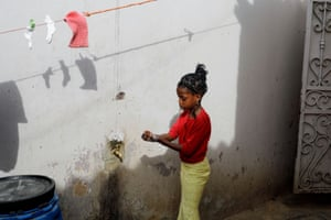 A girl washes her hands at the entrance of her parents house in Pikine, on the outskirts of Dakar, Senegal