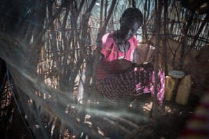 A woman cooks a meal inside her shelter at an IDP camp near Loruk in Baringo County