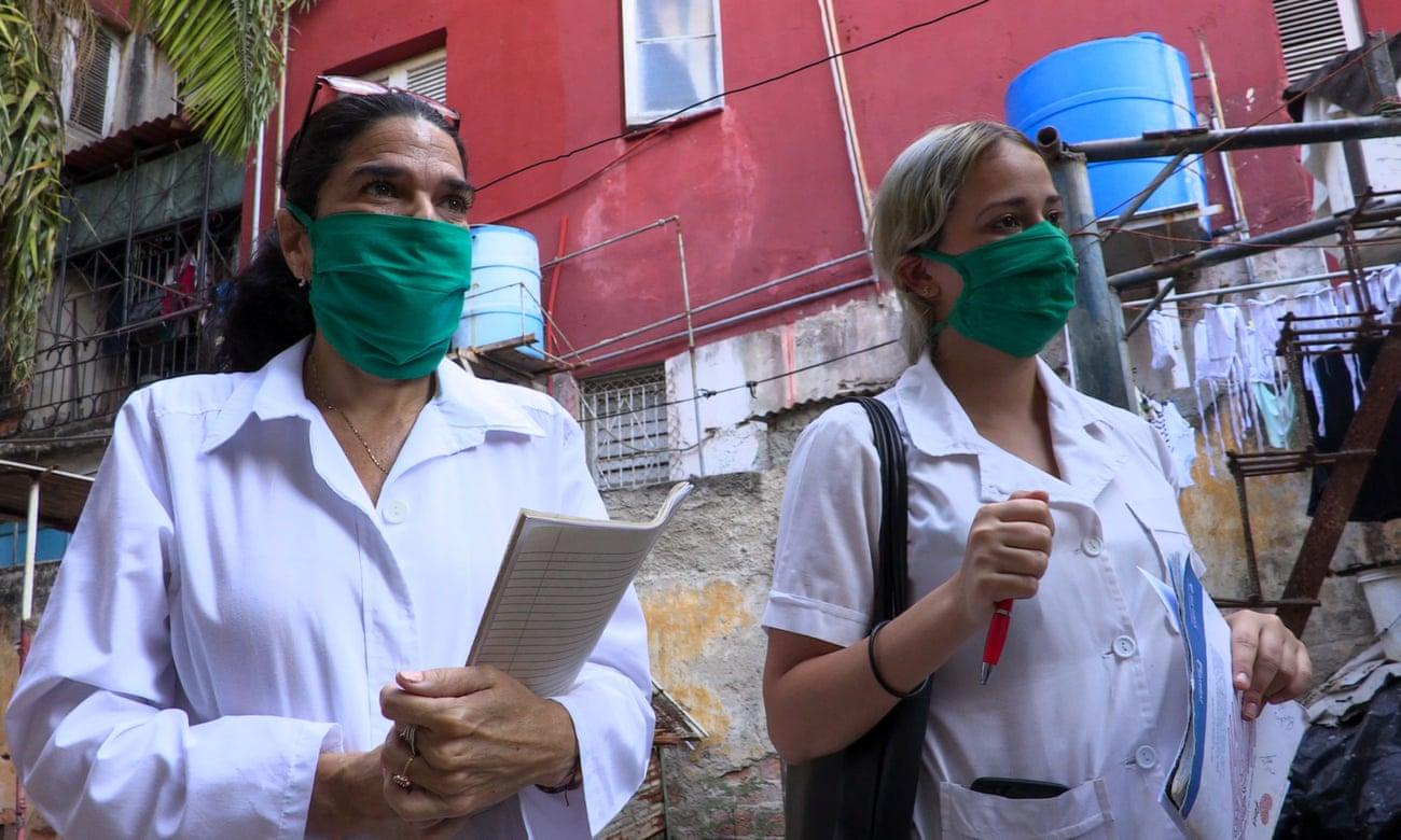 Eine Ärztin und eine Medizinstudentin gehen von Tür zu Tür zu und suchen nach möglichen COVID-19-Fällen   Bildquelle: https://www.theguardian.com/world/2020/jun/07/cuba-coronavirus-success-contact-tracing-isolation © TAdalberto Roque/AFP via Getty Images   Bilder sind in der Regel urheberrechtlich geschützt