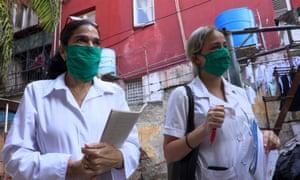 Dr Liz Caballero, left, and student Susana Díaz leave El Vedado polyclinic in Havana, to go door by door looking for possible coronavirus cases.