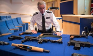 Bernard Hogan-Howe pictured with weapons seized by police officers in London.