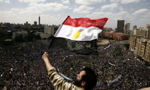 An Egyptian protester waving the national flag as tens of thousands gather for a demonstration at Cairo's Tahrir Square in January 2011.