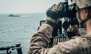A US Marine observes an Iranian craft in the Strait of Hormuz