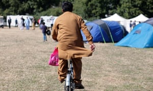An attendee of the UK's largest Muslim convention, Jalsa Salana, rides a bicycle through a field of tents