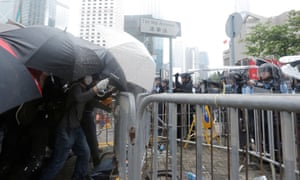 Protesters cower under umbrellas to protect themselves from pepper spray attacks from the police