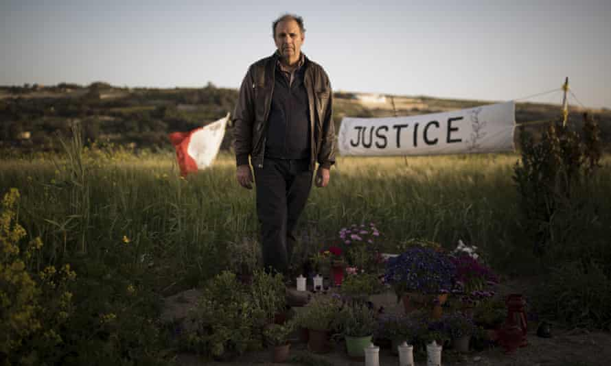 Peter Caruana Galizia stands among tributes to his wife at the scene of her murder.