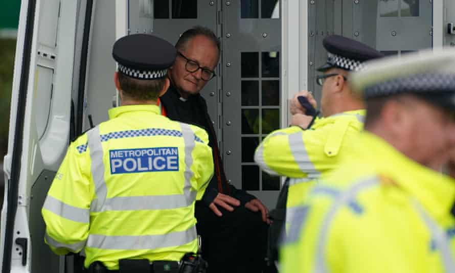 Police officers put an Insulate Britain protester wearing a dog collar into the back of a van after he was detained while occupying a roundabout leading from the M25 motorway to Heathrow on Monday.