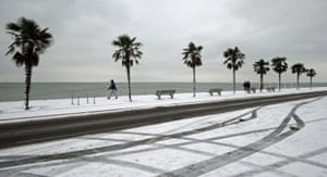 A pedestrian passes palm trees on the snow-covered seafront at Southend-on-Sea in Essex