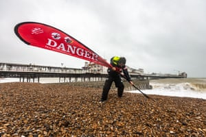 Brighton seafront manager Chris Ingalls secures Danger signs on Brighton Beach as Storm Brendan batters the south coast
