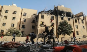 People in Gaza inspect the rubble of a building damaged during Israeli airstrikes
