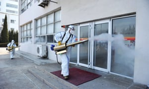 Workers in protective suits spray disinfectant at a business in Qingdao, Shandong province.
