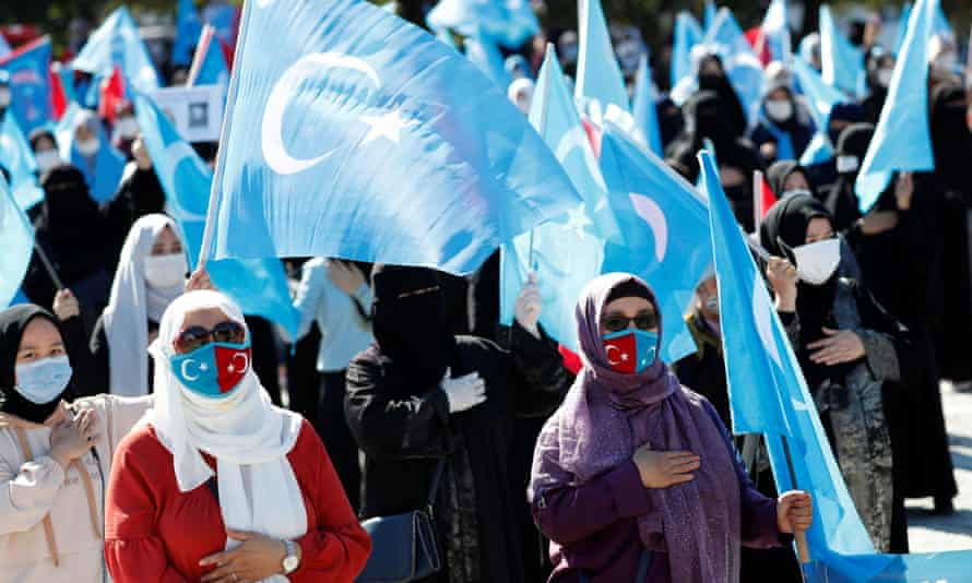 Uighur women wave East Turkestan flags during a protest against China in Istanbul in October