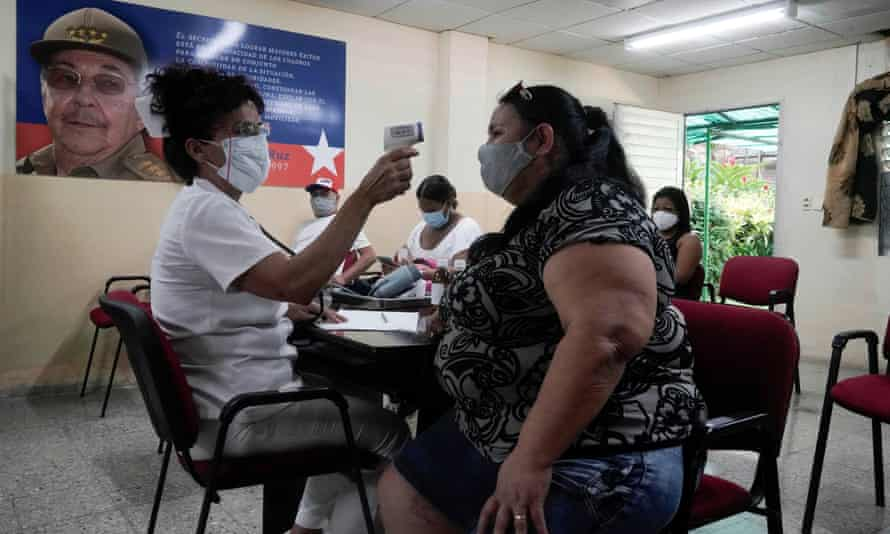 A woman has her temperature checked after receiving a dose of the Abdala vaccine at a vaccination center next to an image of Cuba's former president Raúl Castro in Havana this month.