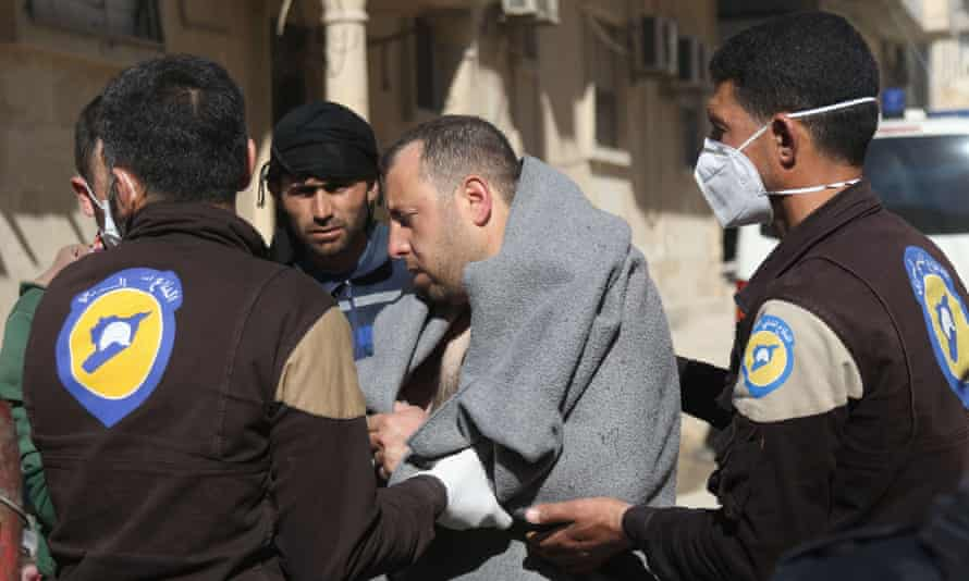 A Syrian man is escorted by civil defence workers in Khan Sheikhun.