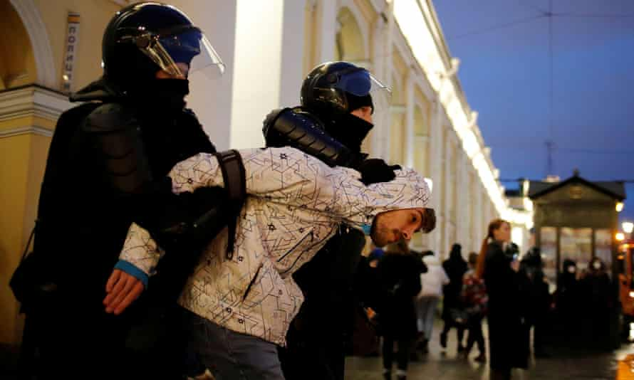 A demonstrator is taken away by law enforcement officers during a rally in support of jailed opposition figure Alexei Navalny in St Petersburg