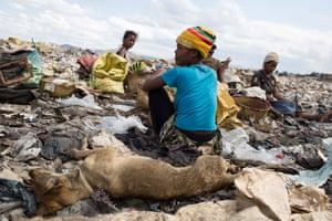 Woman sort through metals, coal and plastic before bagging them up to sell.