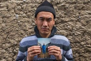 Asylbek, approximately 30 years old, holds a portrait of his brother who disappeared without a trace in early 2013, after working in Russia for 13 years. Their mother died in March 2013, and the family has no way of informing him. Batken city, Batken oblast.
