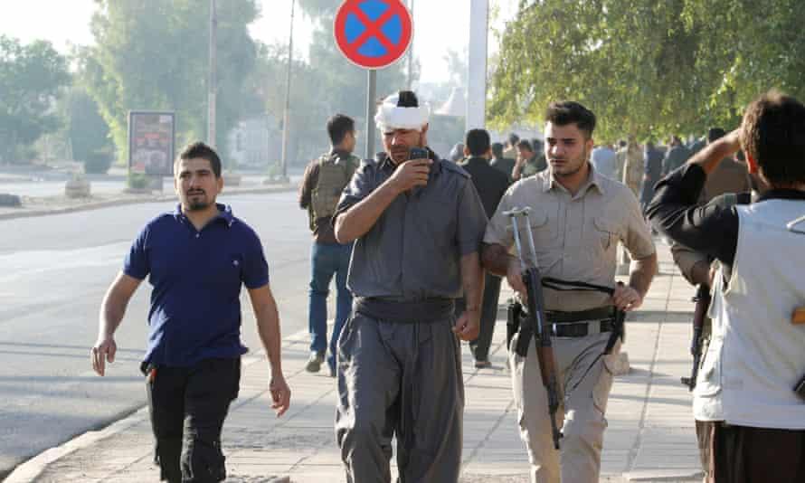 An injured Kurdish man walks at a site of an attack by Islamic State militants in Kirkuk, Iraq.