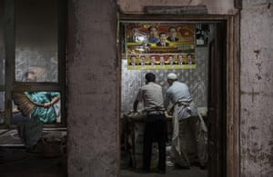 Ethnic Uyghur men make bread at a local bakery under a poster showing Chinese leaders including the late Mao Zedong and the present President Xi Jinping