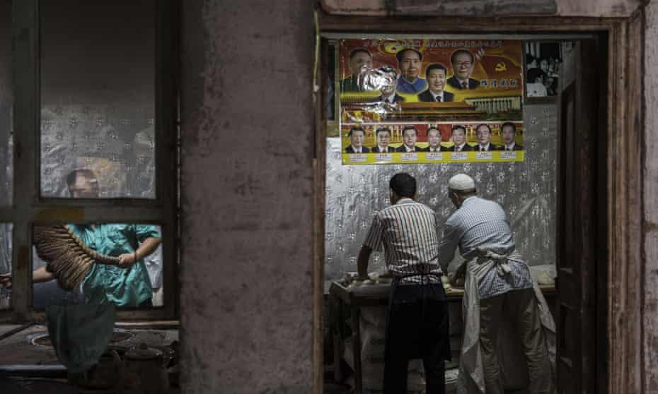Uighur bakers in Kashgar, under a poster of Chinese leaders including Mao Zedong and Xi Jinping.