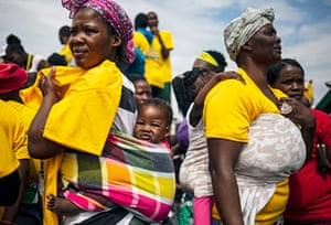 Two mothers carry their children on their backs as they wait for ANC President Ramaphosa to address party supporters during the election campaign in Diepsloot township, Johannesburg, South Africa, 4 April 2019