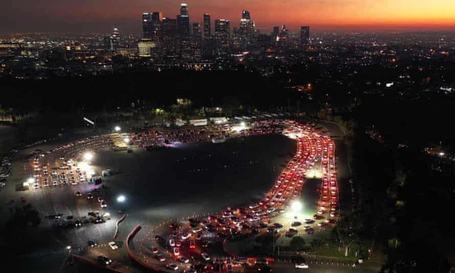 In an aerial view from a drone, cars are lined up at Dodger Stadium for Covid-19 testing as dusk falls over downtown Los Angeles.