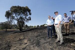 Australian Prime Minister Scott Morrison and SA Premier Steven Marshall (left) stand on burnt ground of Jacaranda Drive in Woodside, South Australia.