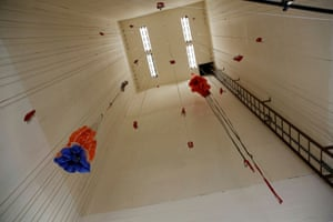 Parachutes hang from ropes in the ceiling to dry after use at the base in West Yellowstone.