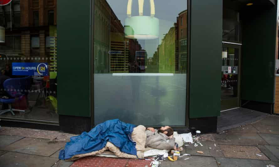 A homeless man finds refuge outside a branch of McDonald's in Manchester city centre.