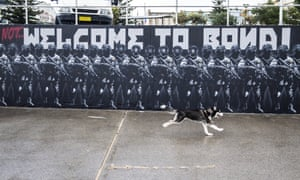A dog runs past artist Luke Cornish's controversial 'Not … Welcome to Bondi' Beach wall mural, which was defaced on Tuesday night.