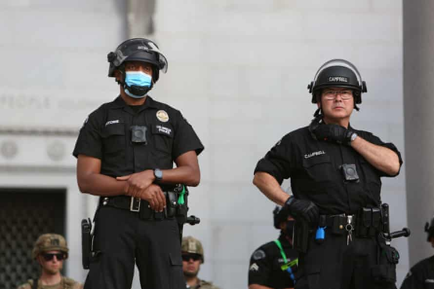 Police keep a watchful eye on a peaceful Black Lives Matter protest outside Los Angeles' city hall on 2 June 2020.