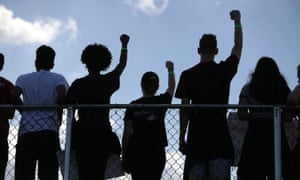Marjory Stoneman Douglas high school students hold their fists up in the air as they participate in the March For Our Lives.