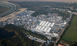 An aerial view shows white containters, tents and makeshift shelters on the eve of the evacuation and dismantlement of the camp.