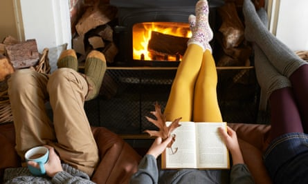 People reading and relaxing in front of the fire