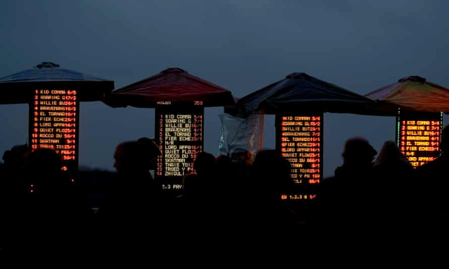 The bookmakers boards shine bright as night falls at Ascot in November