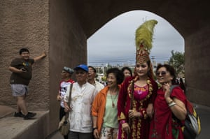 Chinese tourists pose with a performer after a show for tourists in the old town