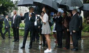Taking shelter from the pouring rain under umbrellas, the president and his daughter Malia look at the 18th-century cathedral of San Cristóbal
